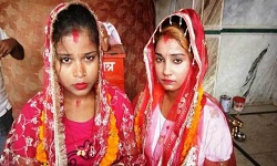 Two girls exchange garlands, apply vermilion at Varanasi temple